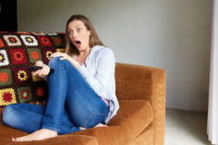 Woman with surprised face expression watching tv Royalty Free Stock Photography