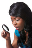 Woman surprised with magnifying glass Stock Image