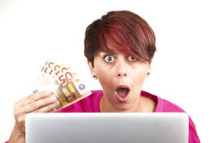 Woman surprised by the money earned. Woman working with laptop surprised by the money earned Stock Photos