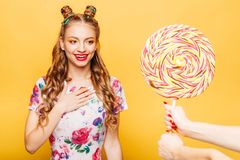 Woman surprised somebody gives her huge lollypop. Beautiful young woman surprised somebody gives her huge lollypop. Bright girl with blonde curly hair. Stylish Stock Images