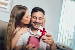 Woman surprising his boyfriend with a gift on the couch at home stock images