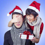 Woman surprising man with gift for New Year. Beautiful smiling young couple celebrating New Year. Attractive women covering man's eyes with a hand, surprising Royalty Free Stock Photography