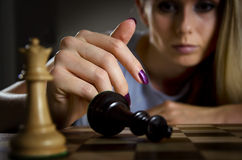 Woman surrendering her king in chess Royalty Free Stock Photography