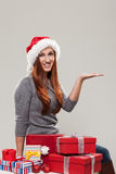 Woman surrounded by Christmas presents. Woman wearing a santa hat surrounded by decorative red Christmas presents sitting on the floor with her empty palm Stock Images