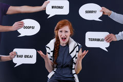 Woman surrounded by comments in speech bubbles. Angry woman surrounded by negative comments in white speech bubbles Stock Photography