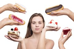 Far to much to choice from. Woman surrounded by many cakes Royalty Free Stock Photo
