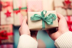 Woman surrounded by many wrapped christmas presents, holding beautifully wrapped tiny vintage present, point of view Royalty Free Stock Images