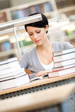 Woman surrounded with piles of books Royalty Free Stock Image
