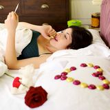 Woman surrounded by San Valentine gifts and chocolate Stock Photography
