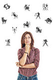 Woman surrounded with zodiac signs thoughtfully looking up with Royalty Free Stock Photos