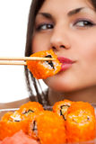 Woman with sushi. Beautiful young woman eating sushi california roll . Shallow depth of field, focus is on the sushi. isolated, studio Royalty Free Stock Photos