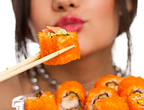 Woman with sushi. Beautiful young woman eating sushi california roll . Shallow depth of field, focus is on the sushi. isolated, studio Royalty Free Stock Images