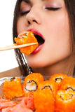 Woman with sushi. Beautiful young woman eating sushi california roll . Shallow depth of field, focus is on the sushi. isolated, studio Stock Image