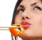 Woman with sushi. Beautiful young woman eating sushi california roll . Shallow depth of field, focus is on the sushi. isolated, studio Stock Images