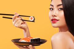 Closeup portrait of asian woman eating sushi and rolls on a yellow background. Royalty Free Stock Photography