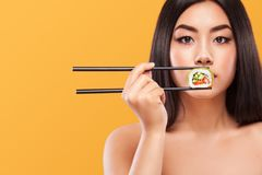 Closeup portrait of asian woman eating sushi and rolls on a yellow background. Copyspace. Royalty Free Stock Image