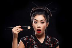 Surprised Asian woman eating sushi and rolls on a black background. Woman with sushi woman eating sushi and rolls on a light background stock photography