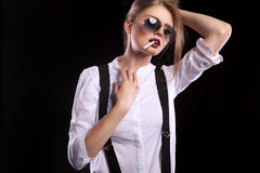 Woman with suspenders smoking sensual a cigarette Royalty Free Stock Photo