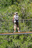 Woman on a suspension bridge Stock Photography