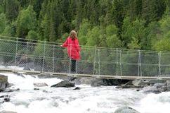 Woman on suspension bridge stock photo