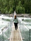 Woman on suspension bridge royalty free stock image
