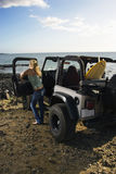 Woman with SUV at the Beach Stock Photo