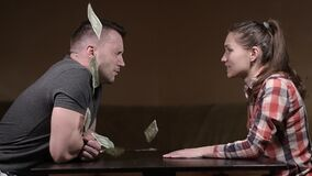 A woman swears at a man and throws money in his face. Husband and wife