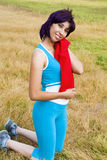 Woman sweat. Smiling Woman cleans sweat after exercising in a field Stock Photo