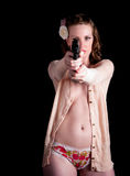 Woman in sweater aiming a gun. A beautiful young woman in open front sweater aims a hand gun directly at the camera isolated on a black background as she blends royalty free stock images