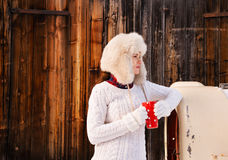 Woman in sweater and furry hat with cup near rustic wood wall Stock Images