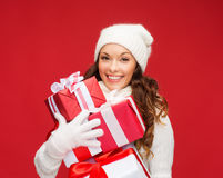 Woman in sweater and hat with many gift boxes Stock Image
