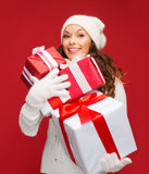 Woman in sweater and hat with many gift boxes Stock Photography