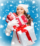 Woman in sweater and hat with many gift boxes Royalty Free Stock Photo