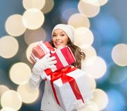 Woman in sweater and hat with many gift boxes Royalty Free Stock Images