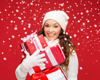 Woman in sweater and hat with many gift boxes Stock Photos