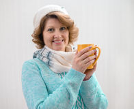 Woman in sweater, hat and scarf holding yellow cup of tea Royalty Free Stock Photos