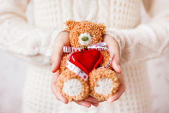 Woman in sweater holding toy bear with christmas ribbon and heart. Royalty Free Stock Images