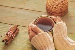 Woman in sweater holds cup of tea on wooden table Royalty Free Stock Images