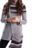 Woman in sweater holds phone. Stock Photo