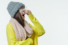 Woman in a sweater, knitted hat, scarf sneezes with a handkerchief. Season of the common cold, viruses, rhinitis. White background, copy space Royalty Free Stock Photography