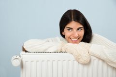 Woman in sweater leaning on radiator Royalty Free Stock Photos