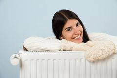 Woman in sweater leaning on radiator Royalty Free Stock Photo