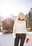 Woman in sweater looking up while standing near mountain house Stock Photo