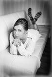 Woman in sweater lying on a sofa Stock Image