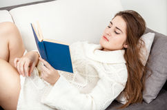 Woman in sweater lying on sofa and reading book Stock Photography