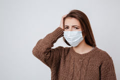 Woman in sweater and medical mask Stock Photo