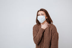 Woman in sweater and medical mask holding her neck Stock Photos