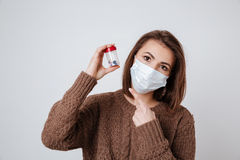 Woman in sweater and medical mask holding tablets Royalty Free Stock Image