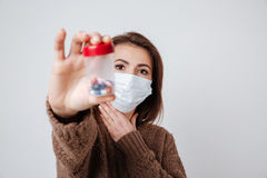 Woman in sweater and medical mask holding tablets Royalty Free Stock Photography