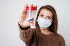 Woman in sweater and medical mask with tablets Stock Photo
